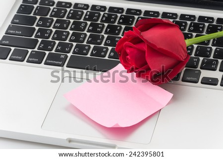 red rose with pink paper note on laptop - stock photo