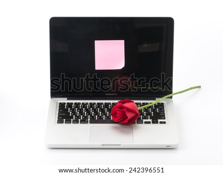 red rose with pink paper note on laptop