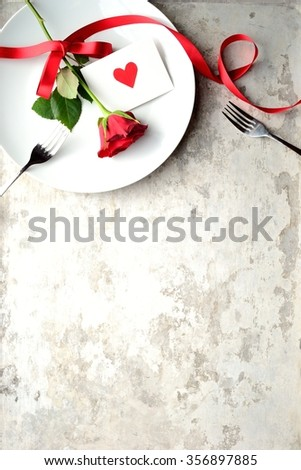 Red rose with red heart message card on the white dish.Image of meal on Valentines day - stock photo