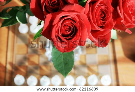Red Roses  above a Chess board on a wooden table - stock photo