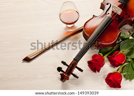 Red roses and a violin on the table - stock photo