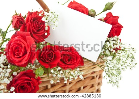 Red roses and blank invitation card in wicker basket - stock photo