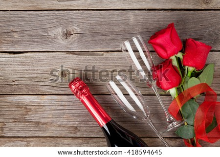 Red roses and champagne over wooden background. Top view with copy space - stock photo
