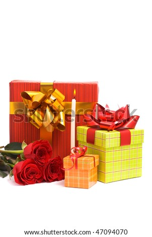Red roses and gift boxes on a studio white background.