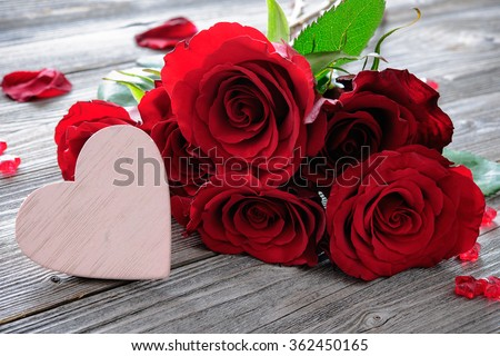 Red roses and heart on wooden background. Valentines day background - stock photo