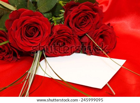 Red roses and invitation card on silk background - stock photo