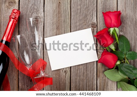 Red roses, champagne and blank greeting card over wooden background. Top view with copy space - stock photo