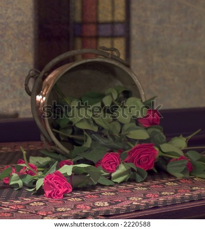 Red roses falling from copper vase in front of old mirror glass