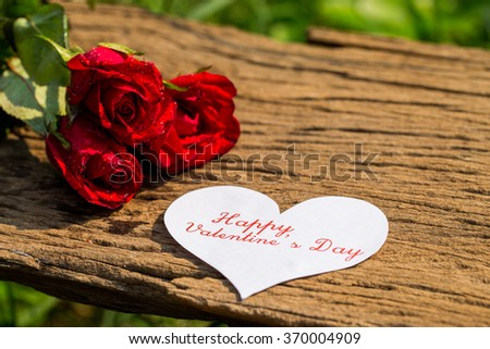 Red roses for valentine's day on wooden background. Closeup.