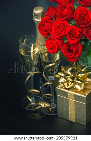red roses, golden gift box and and champagne on black background. festive flower arrangement. selective focus. retro style toned picture - stock photo