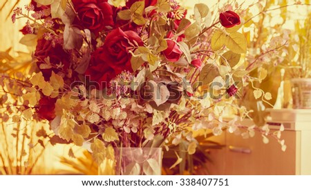 Red roses in a glass vase vintage - stock photo