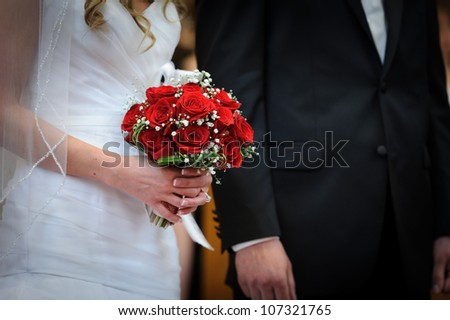 Red roses in brides hands - stock photo