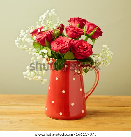 Red roses in polka dots jug on wooden table - stock photo