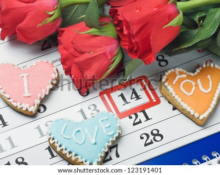 """red roses lay on the calendar with the date of February 14 Valentine's day and cookies with the words """"I love you"""" - stock photo"""