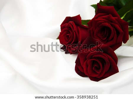 Red roses on a white  satin background