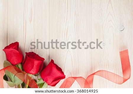 Red roses on wooden background. Valentines day background - stock photo