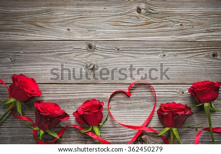 Red roses on wooden board, Valentines Day background - stock photo