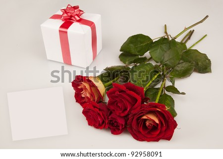 red roses, white gift and card on a white background
