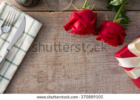 Red roses with gift box on dining table.  Valentine's Day, anniversary etc. - stock photo