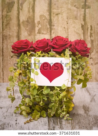 Red roses with heart on card - stock photo