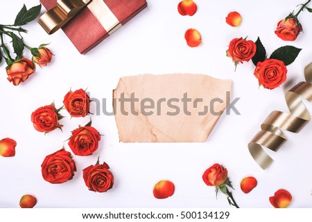 Red roses with red gift and blank vintage sheet of paper on white background. Flat lay, top view