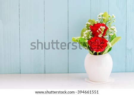 Red roses with white daisy flower and green leaf at white vase on white and blue wooden background - stock photo