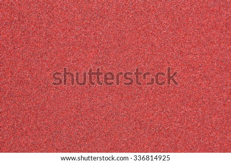 Red rough textured sandpaper background, close up