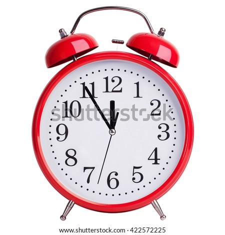 Red round alarm clock shows five minutes to twelve - stock photo
