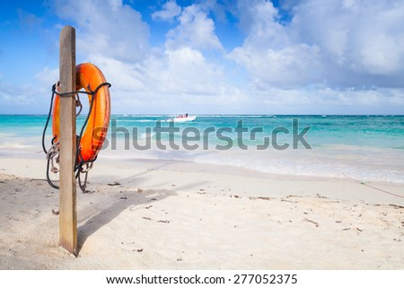 Red round life buoy hanging on wooden pole, empty sandy beach of Dominican republic