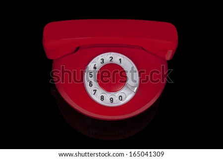 Red round retro phone from the sixties isolated on black background. Retro nostalgia objects. - stock photo