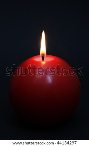 Red round shining candle isolated on a black background