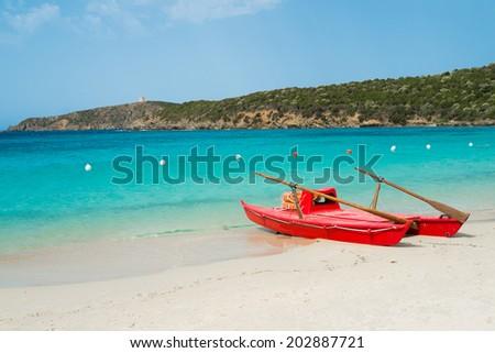 Red rowboat on Tuerredda beach along the coast of Teulada, South Sardinia, Italy - stock photo