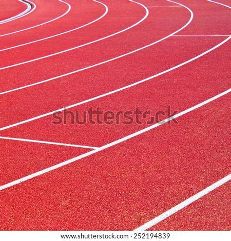 Red running racetrack on the stadium - stock photo