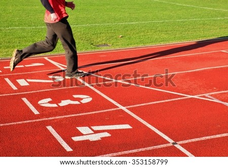 Red running racetrack on the stadium with two running legs
