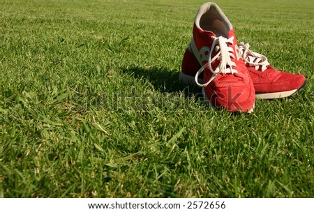 Red running shoes with white laces on a green sporting field