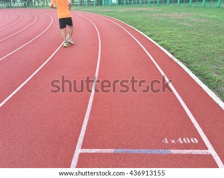 Red running track and green grass