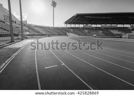 Red running track in stadium , black and white.