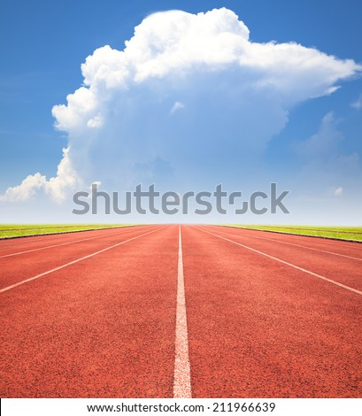 red running track over blue sky and clouds - stock photo
