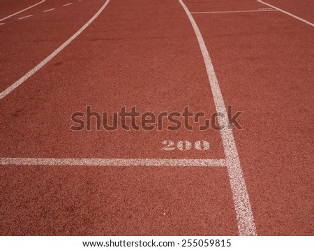 Red running track with white lines and 200 mark - stock photo