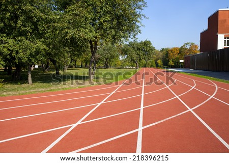 Red running tracks in sport stadium in autumn park - stock photo