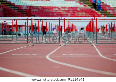 red running tracks with hurdles set up for training - stock photo