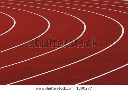 red running tracks with white dividing lines with a left hand turn - stock photo