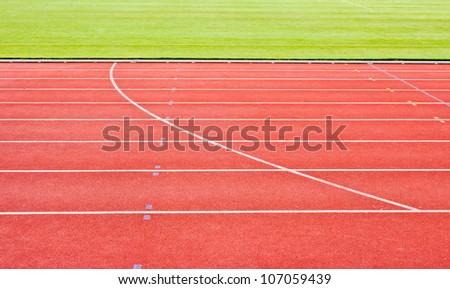 red running tracks with white start numbers at stadium closeup - stock photo