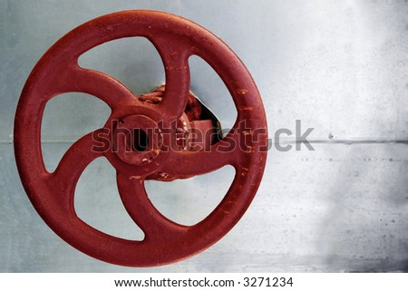 red rusty industrial faucet wheel on silver background - stock photo
