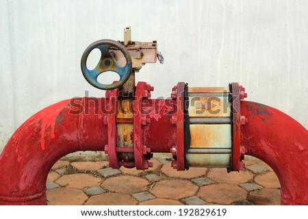 red rusty metal industrial water pipes with a valve. - stock photo