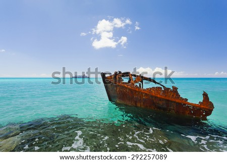 Red rusty shipwreck in tropical turquoise waters with boat on the horizon.  - stock photo