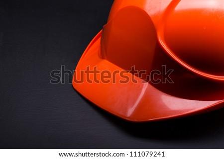 Red safety helmet on black - stock photo