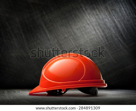 Red safety helmet on steel scratchy background - stock photo