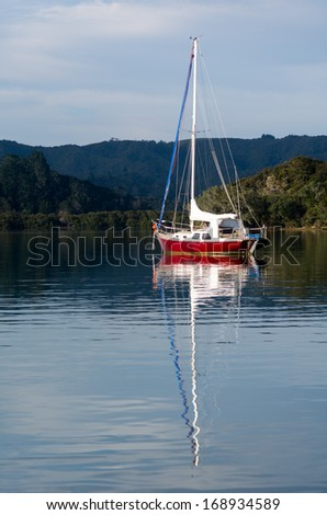 Red sail yacht mooring in the bay of Islands New Zealand. vertical - stock photo