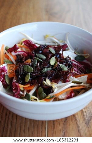 Red salad with carrots, sprouts, pumpkin seeds and seaweed in white bowl on wooden background